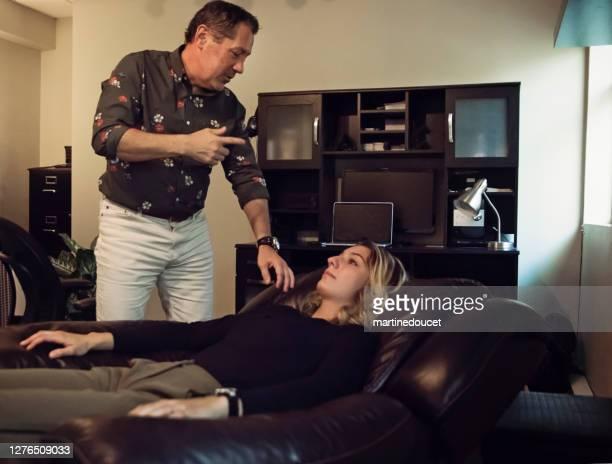 """hipnoterapeuta en sesión con el cliente en la oficina. - """"martine doucet"""" or martinedoucet fotografías e imágenes de stock"""
