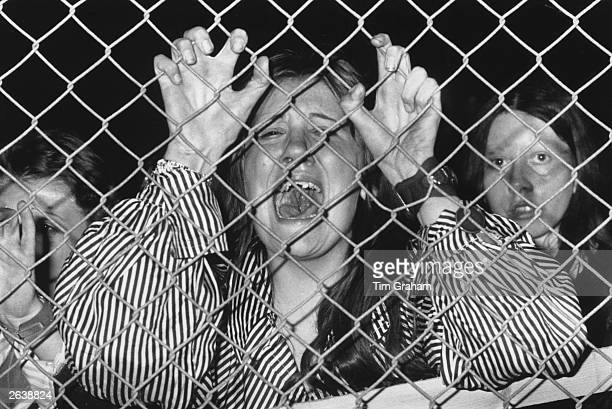 A hysterical fan grasps a wire fence at a David Cassidy concert at White City West London