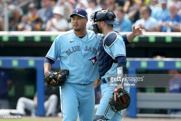Hyun Jin Ryu of the Toronto Blue Jays and teammate Danny Jansen embrace after defeating the Texas Rangers 5-0 in game one of a doubleheader at Sahlen...