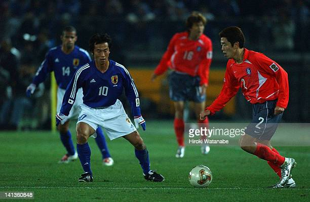 Hyun YoungMin of South Korea and Toshiya Fujita of Japan compete for the ball during the East Asian Football Championship match between Japan and...