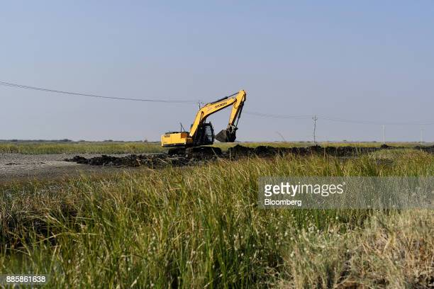 A Hyundai Construction Equipment Inc excavator operates at an under construction sewerage system on the project site for a 920squarekilometer...