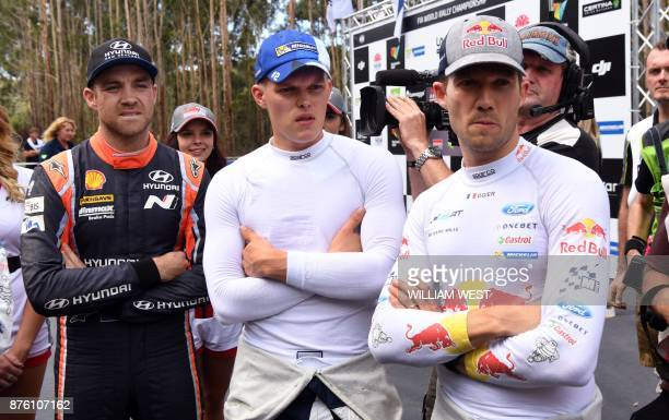 Hyundai driver Hayden Paddon of New Zealand Ford drivers Ott Tanak of Estonia and Sebastien Ogier of France react after watching fellow competitor...