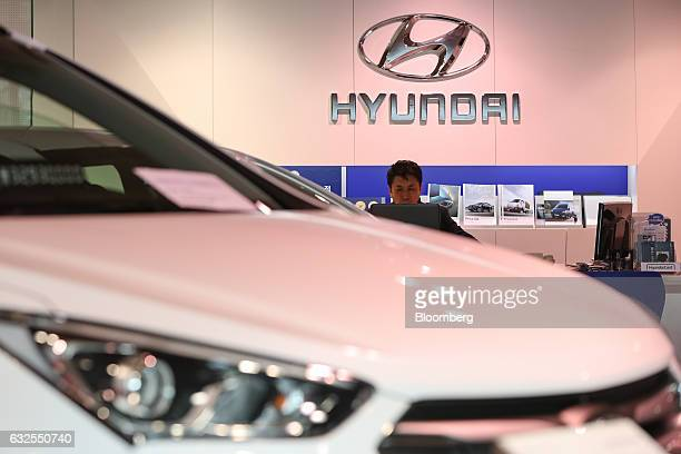 A Hyundai Motor Co employee sits near a vehicle on display at a company dealership in Seoul South Korea on Monday Jan 23 2017 Hyundai South Korea's...