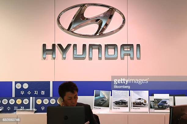 Hyundai Motor Co. Employee speaks on the phone beneath a Hyundai logo at a company dealership in Seoul, South Korea, on Monday, Jan. 23, 2017....