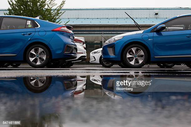 Hyundai Motor Co. Ioniq electric vehicles are reflected in a puddle at the company's plant in Ulsan, South Korea, on Monday, July 4, 2016. South...