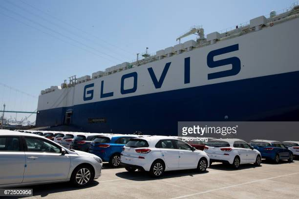 Hyundai Motor Co vehicles bound for export await shipment in front of a Hyundai Glovis Co rollon/rolloff cargo ship at a port near the company's...