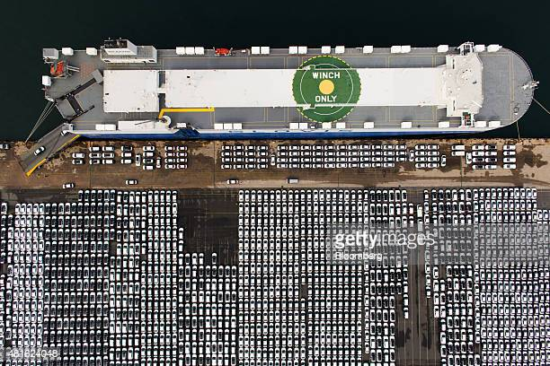 Hyundai Motor Co vehicles bound for export await shipment next to a Hyundai Glovis Co rollon/rolloff cargo ship at a port near Hyundai Motor's Ulsan...