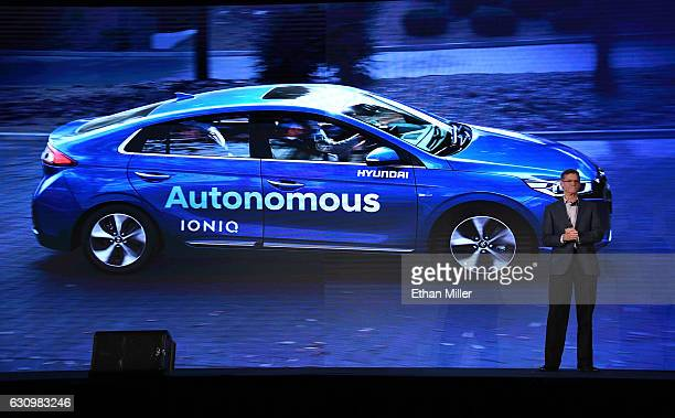 Hyundai Motor Co Vice President Mike O'Brien speaks in front of a video image of the Hyundai autonomous Ioniq vehicle during a press event for CES...