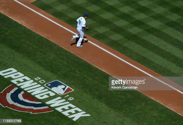 HyunJin Ryu of the Los Angeles Dodgers runs to the pitching mound to start the Opening Day baseball game against Arizona Diamondbacks at Dodger...