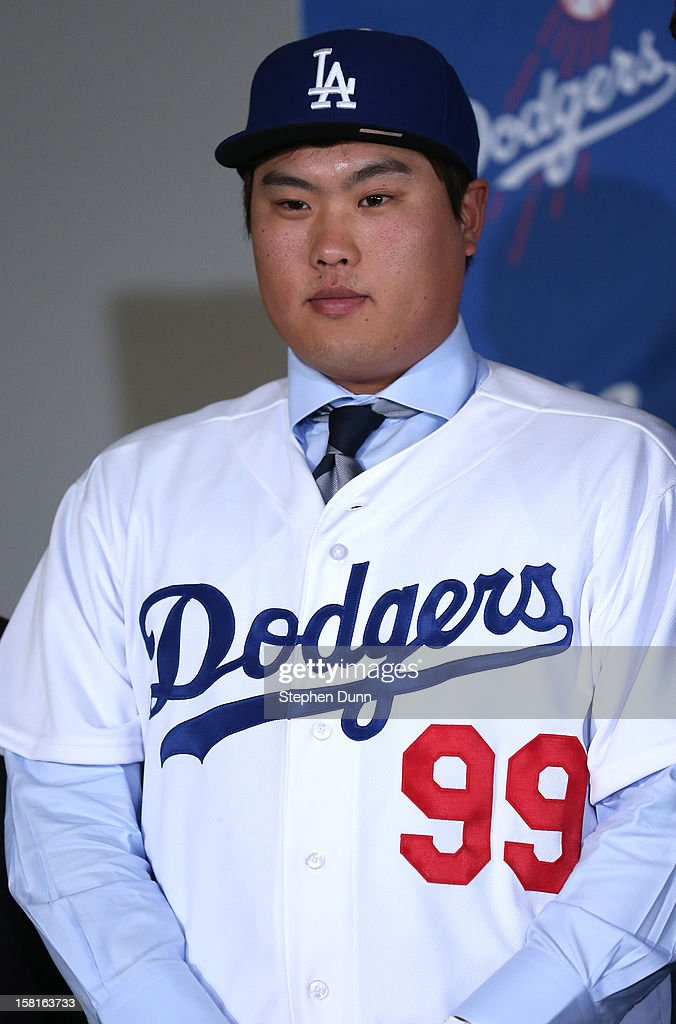 Hyun-Jin Ryu stands in his cap and jersey at a press conference introducing him following his signing with the Los Angeles Dodgers at Dodger Stadium on December 10, 2012 in Los Angeles, California.