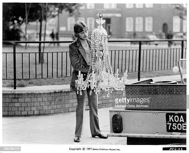 Hywel Bennett looks at a chandelier in a scene from the film 'Percy' 1971 Photo by MetroGoldwynMayer/Getty Images