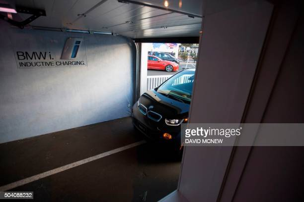 A BMW i3 electric car drives autonomously into a simulated garage to park over an inductive charging station for solar energy at a BMW i Energy...