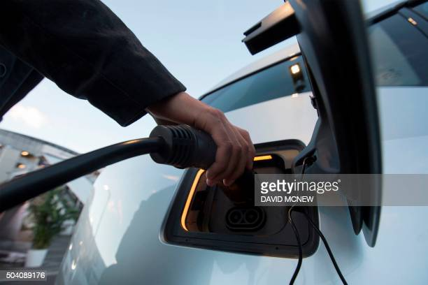 A BMW i3 electric car is plugged into a charging station at the CES 2016 Consumer Electronics Show on January 8 2016 in Las Vegas Nevada AFP PHOTO/...