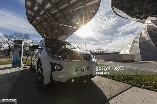 A BMW i3 plugin automobile produced by Bayerische Motoren Werke AG sits beside an electric charging station outside the BMW World showroom in Munich...