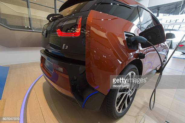 A BMW i3 plugin automobile produced by Bayerische Motoren Werke AG sits connected to an electrical plug inside the BMW World showroom in Munich...