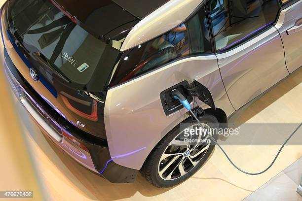 A BMW i3 plugin hybrid automobile manufactured by Bayerische Motoren Werke AG sits connected to a electric charging plug inside the BMW World...