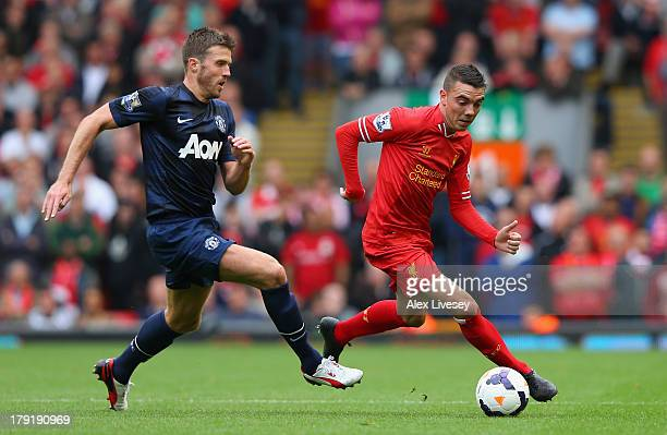 Iago Aspas of Liverpool competes with Michael Carrick of Manchester United during the Barclays Premier League match between Liverpool and Manchester...