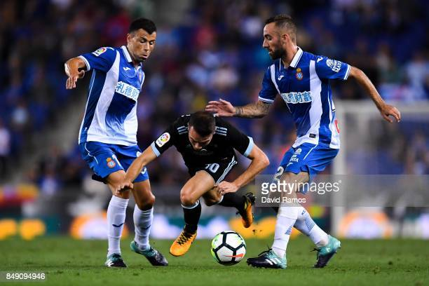 Iago Aspas of RC Celta de Vigo competes for the ball with Javi Fuego and Sergi Darder of RCD Espanyol during the La Liga match between Espanyol and...