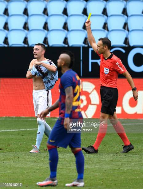 Iago Aspas of RC Celta Vigo is shown a yellow card by the referee after removing his shirt celebrating scoring the second goal during the Liga match...
