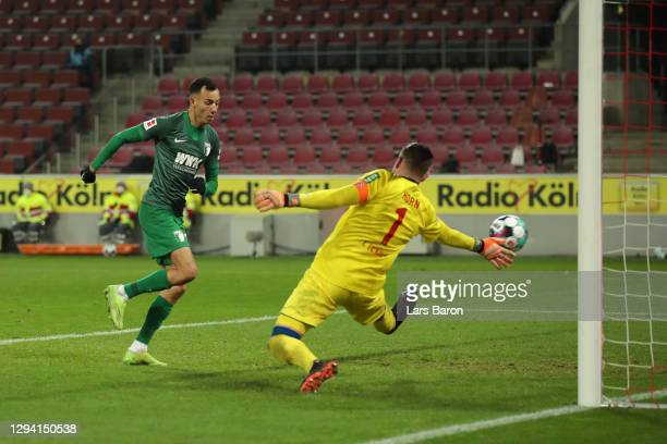 Iago of Augsburg scores his team's first goal against goalkeeper Timo Horn of Koeln during the Bundesliga match between 1. FC Koeln and FC Augsburg...
