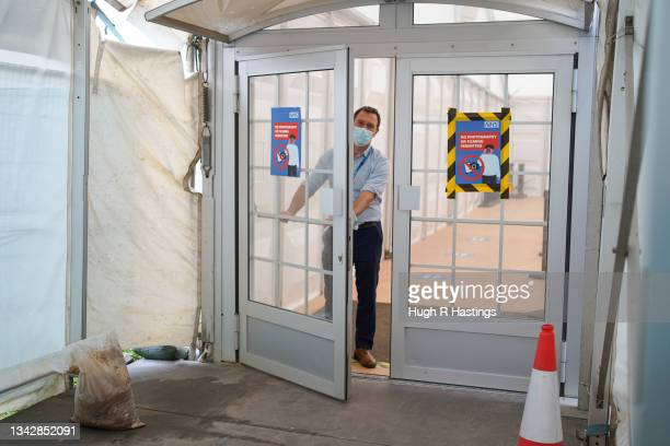Iain Davidson, clinical lead, shuts the doors at the Stithians Showground temporary NHS vaccination centre as it closed on September 26, 2021 in...