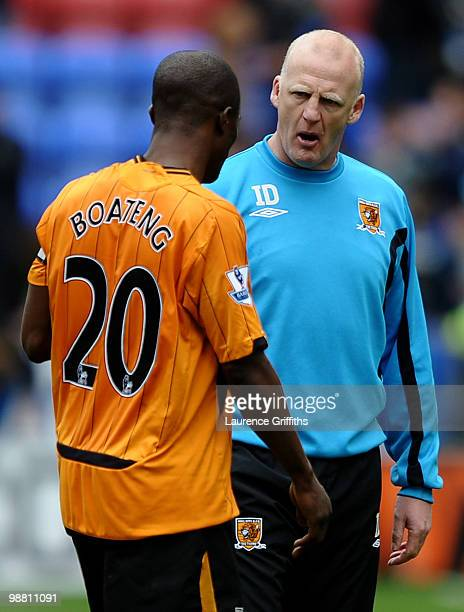 Iain Dowie of Hull City consoles George Boateng after they are relagated during the Barclays Premier League match between Wigan Athletic and Hull...
