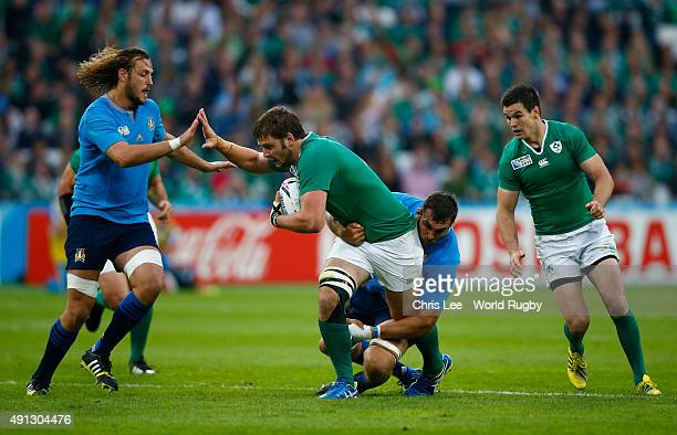 Iain Henderson of Ireland is tackled by Quintin Geldenhuys and Josh Furno of Italy during the 2015 Rugby World Cup Pool D match between Ireland and...