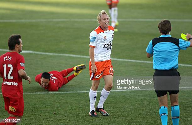 Iain Ramsey of Adelaide lies in pain as Mitchell Nichols of the Roar receives a yellow card for a tackle on Ramsey during the round 21 ALeague match...