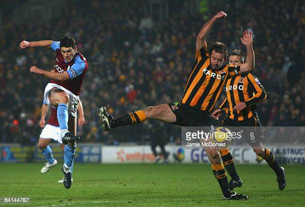 Ian Ashbee of Hull City stretches to block the shot of Gareth Barry of Aston Villa during the Barclays Premier League match between Hull City and...