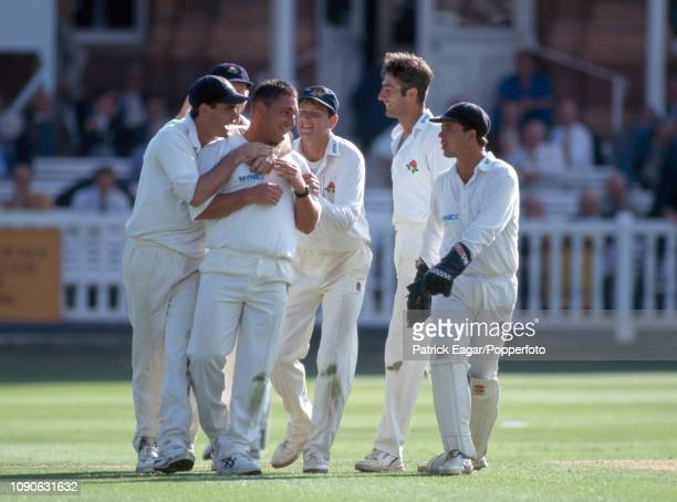 Ian Austin of Lancashire is congratulated by teammates after taking one of his four wickets during the Benson and Hedges Cup Final between Lancashire...