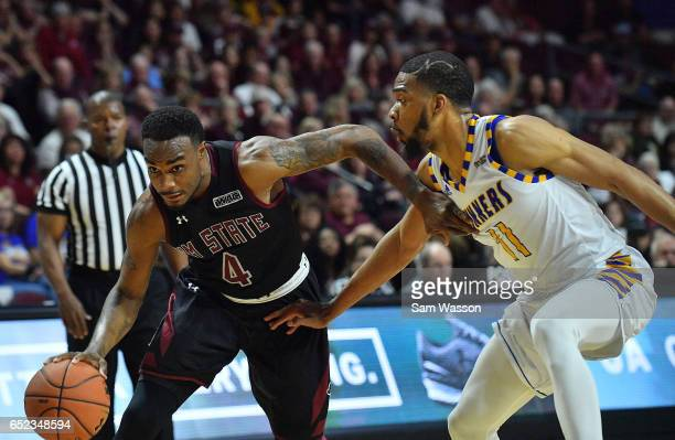 Ian Baker of the New Mexico State Aggies drives against Jaylin Airington of the Cal State Bakersfield Roadrunners during the championship game of the...