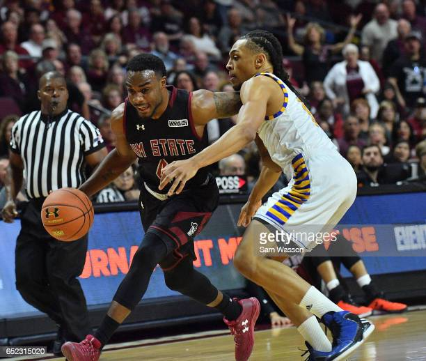 Ian Baker of the New Mexico State Aggies drives against Matt Smith of the Cal State Bakersfield Roadrunners during the championship game of the...