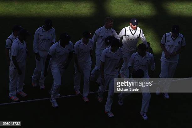 Ian Bell the captain of Warwickshire emerges from the shadows during day one of the Specsavers County Championship Division One match between...