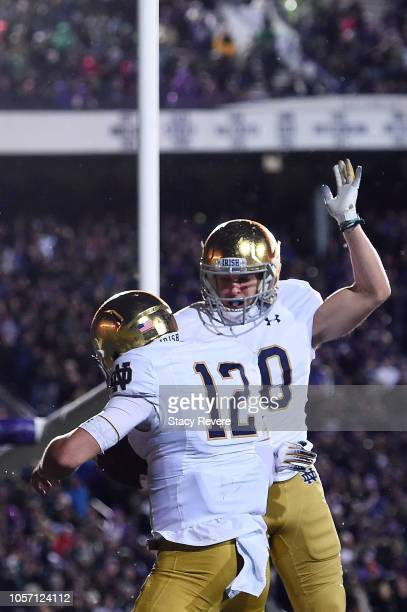 Ian Book celebrates a touchdown with Chris Finke of the Notre Dame Fighting Irish during the second half of a game against the Northwestern Wildcats...