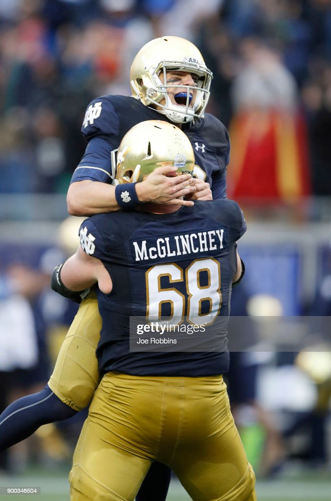 Ian Book #12 of the Notre Dame Fighting Irish is lifted up by Mike McGlinchey #68 after throwing the game-winning 55-yard touchdown to Miles Boykin in the fourth quarter of the Citrus Bowl against the LSU Tigers on January 1, 2018 in Orlando, Florida. Notre Dame won 21-17.