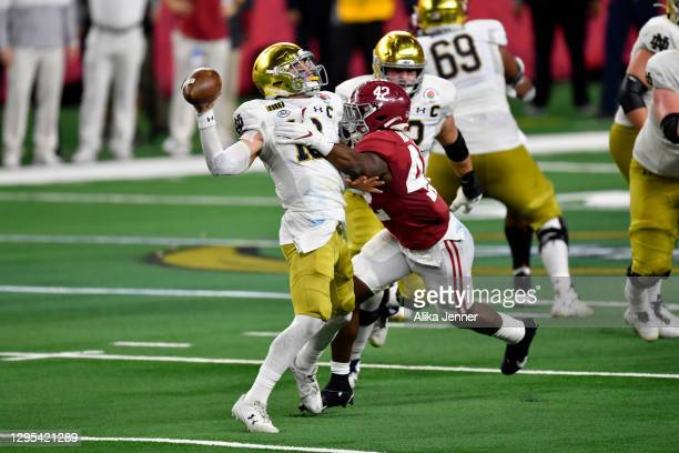 Ian Book of the Notre Dame Fighting Irish is pressured by Jaylen Moody of the Alabama Crimson Tide during the College Football Playoff Semifinal at...