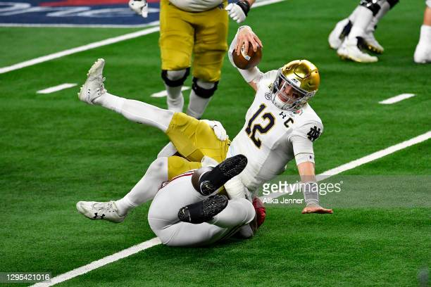 Ian Book of the Notre Dame Fighting Irish is tackled by Byron Young of the Alabama Crimson Tide during the College Football Playoff Semifinal at the...