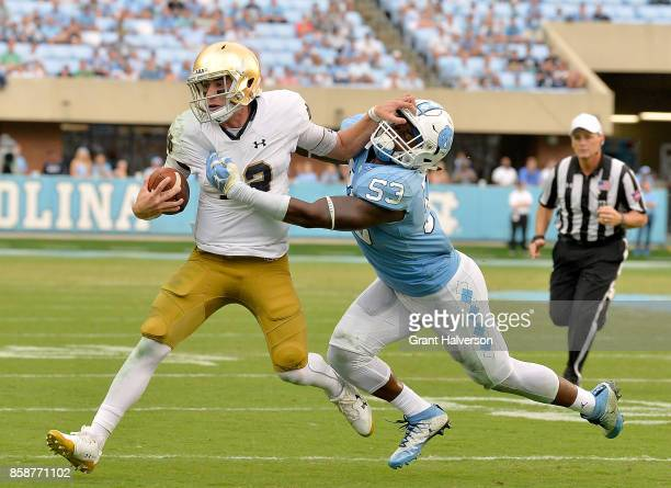 Ian Book of the Notre Dame Fighting Irish stiffarms Malik Carney of the North Carolina Tar Heels during the game at Kenan Stadium on October 7 2017...