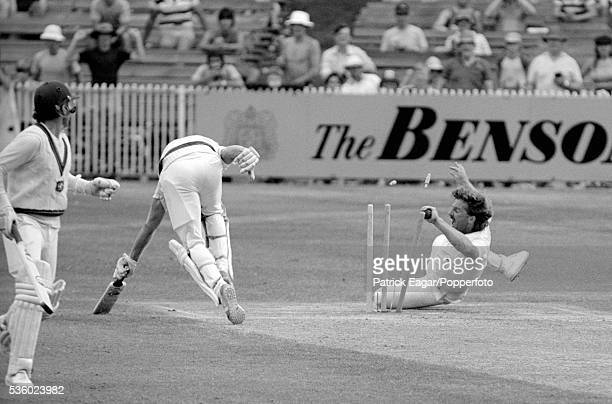 Ian Botham of England attempts to run out Jeff Thomson of Australia as Allan Border looks on during the 4th Ashes Test match between Australia and...