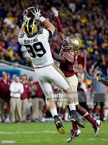 Ian Bunting of the Michigan Wolverines completes a first down pass against the defense of AJ Westbrook of the Florida State Seminoles in the third...