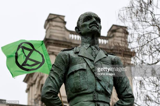 Ian Christian Smuts sculpture with an Extinction Rebellion Flag Extinction Rebellion protesters march from Marble Arch to Parliament Square...