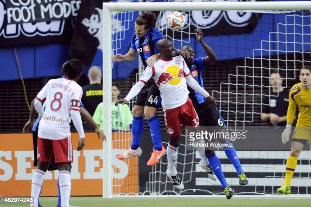 Ian Christianson of the New York RedBulls jumps the head the ball in front of Heath Pearce and Hassoun Camara of the Montreal Impact during the MLS...
