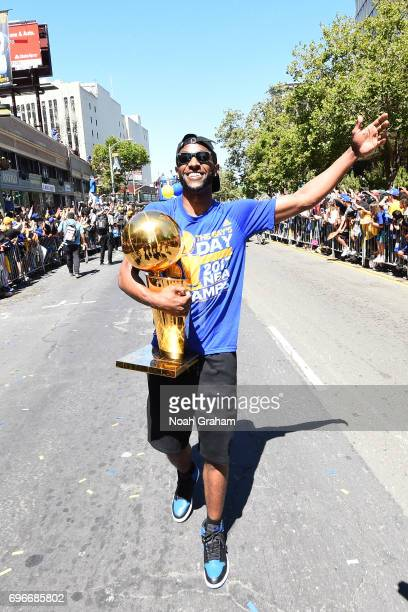 Ian Clark of the Golden State Warriors walks with the Larry O'Brien Trophy during the Victory Parade and Rally on June 15 2017 in Oakland California...
