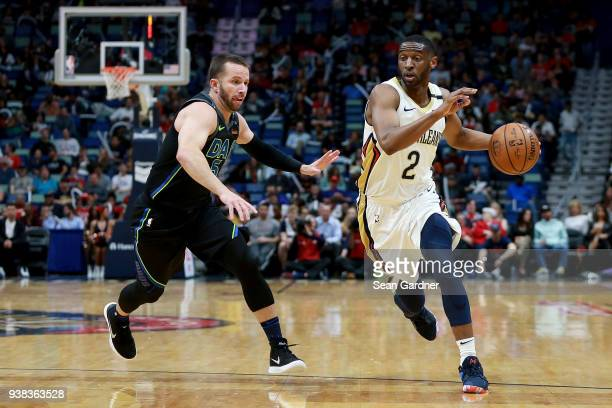 Ian Clark of the New Orleans Pelicans drives by JJ Barea of the Dallas Mavericks during the first half of a NBA game at the Smoothie King Center on...