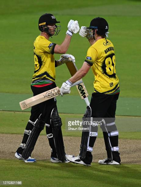 Ian Cockbain of Gloucestershire is congratulated by team mate Miles Hammond after reaching 50 during the T20 Vitality Blast 2020 match between...