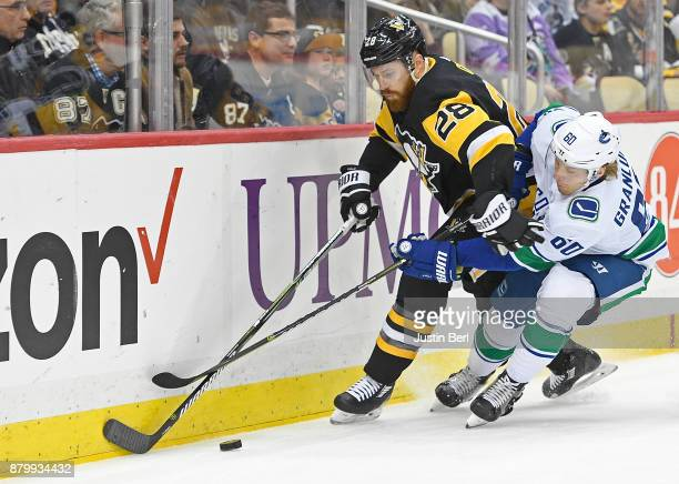 Ian Cole of the Pittsburgh Penguins battles for the puck along the boards with Markus Granlund of the Vancouver Canucks in the first period during...