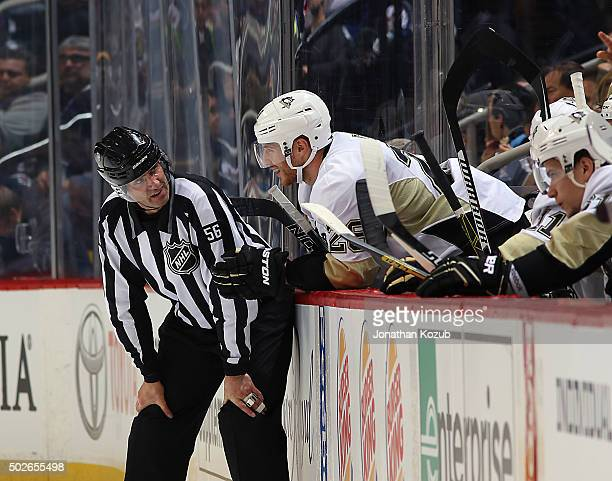 Ian Cole of the Pittsburgh Penguins chats with linesman Mark Wheler from the bench during a first period stoppage in play against the Winnipeg Jets...