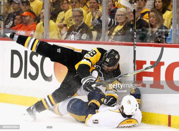 Ian Cole of the Pittsburgh Penguins falls to the ice after checking Filip Forsberg of the Nashville Predators to the boards during the third period...