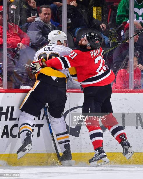 Ian Cole of the Pittsburgh Penguins is checked into the boards by Kyle Palmieri of the New Jersey Devils during an NHL game at Prudential Center on...