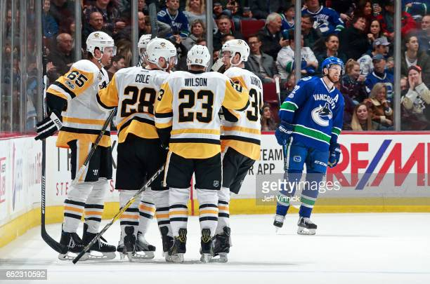 Ian Cole of the Pittsburgh Penguins is congratulated by teammates Scott Wilson, Tom Kuhnhackl, and Ron Hainsey after scoring during his NHL game...